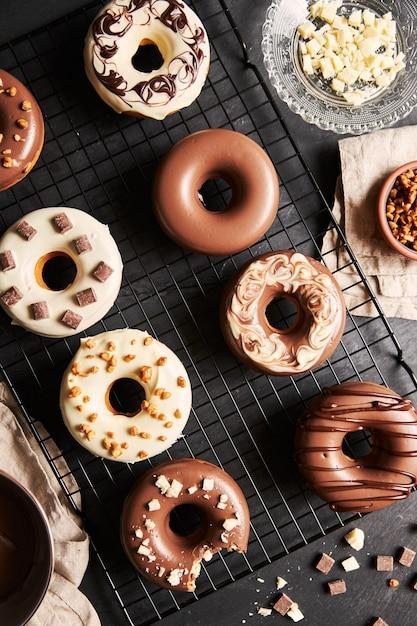 Deliziose ciambelle ricoperte di glassa di cioccolato bianco e marrone con gli ingredienti su un tavolo Foto Gratuite