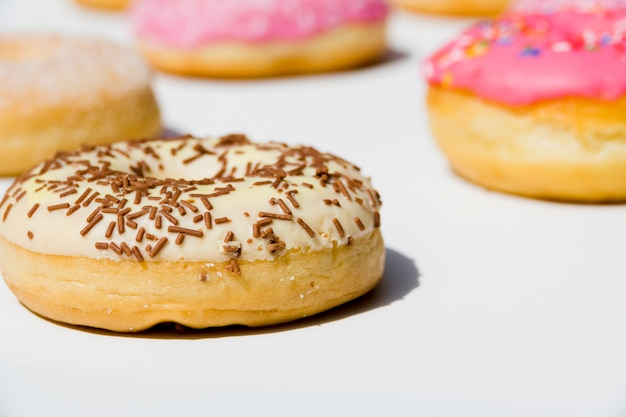 Delicious donuts with sprinkles on white backdrop Free Photo