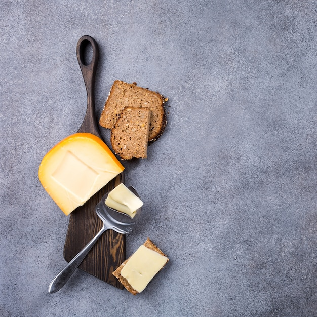 Delicious dutch gouda cheese with cheese slices, multigrain bread and special knife on old wooden board. Premium Photo