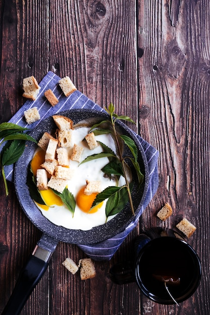 Delicious eggs and tea breakfast on wooden table Free Photo