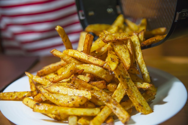 Delicious french fried potato mix with chilly powder on wooden table Free Photo