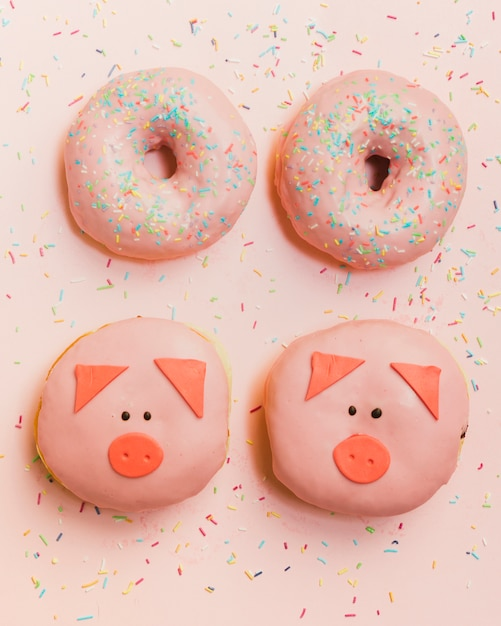 Delicious fresh decorated donuts arranged on pink wallpaper Free Photo