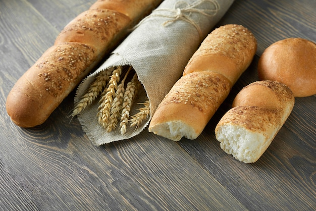 Delicious fresh french baguettes and millets wrapped in craft paper on wooden worktop copyspace store shop market supermarket food retail organic natural recipe eating concept. Free Photo