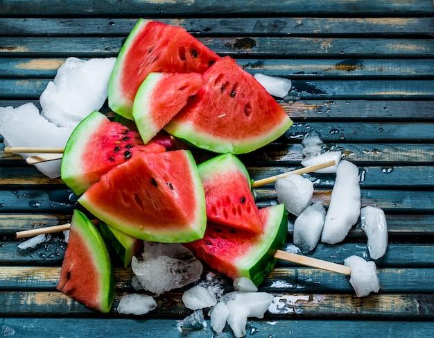 美味しい新鮮なスイカ。スイカとアイスクリーム。青い木製の背景においしいスイカ。閉じる。 無料写真