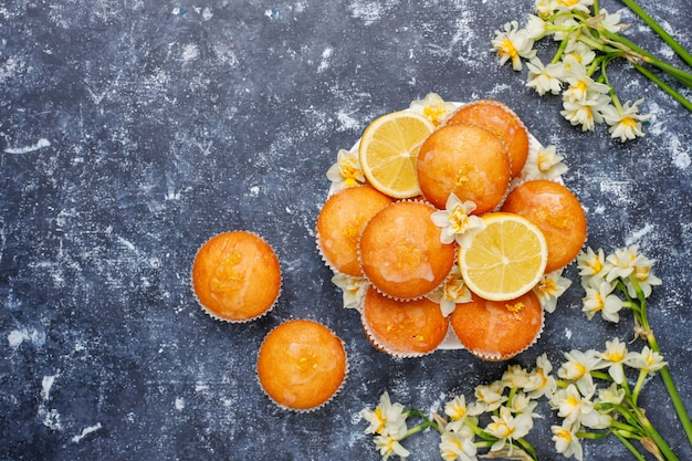 Delicious freshly baked homemade lemon muffins with lemons on a plate Free Photo