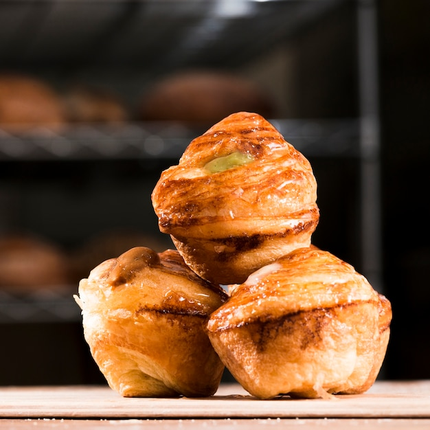Delicious freshly baked sweet puff pastry on plank over the wooden table Free Photo