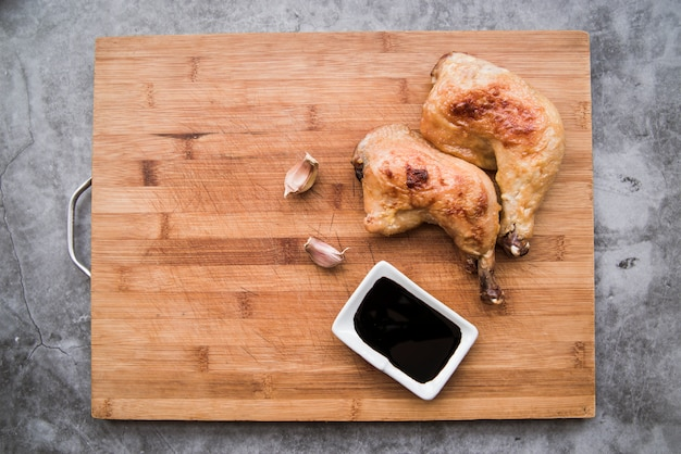 Delicious grilled chicken legs with soy sauce and garlic on cutting board Free Photo