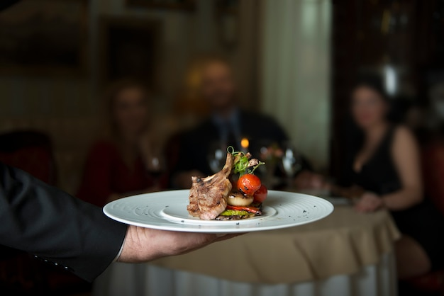 Delicious grilled lamb ribs, served with grill tomato and decorated with radish Premium Photo