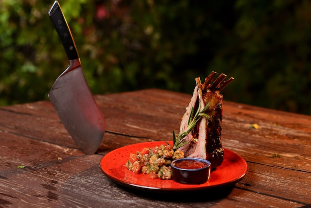 Delicious grilled ribs with sauce. in a red plate on a wooden table Premium Photo