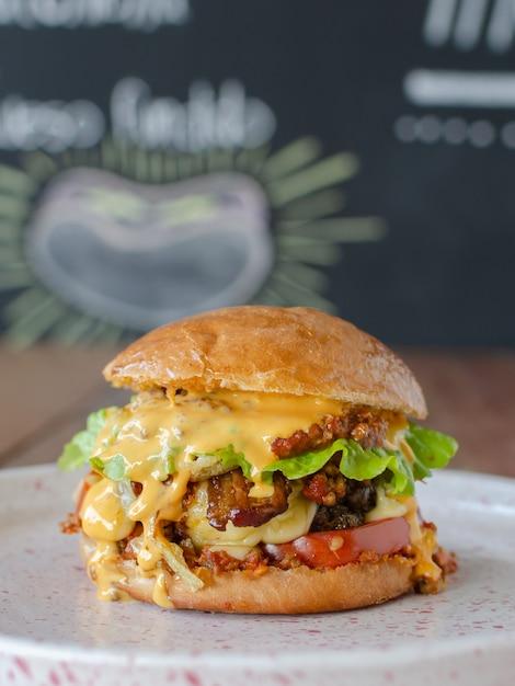 Вкусный гамбургер с чили и чесс, фон доске Premium Фотографии