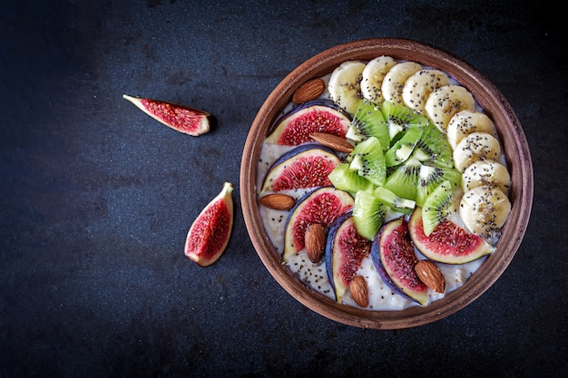 Delicious and healthy oatmeal with figs, kiwi, banana, almond and chia seeds. Premium Photo