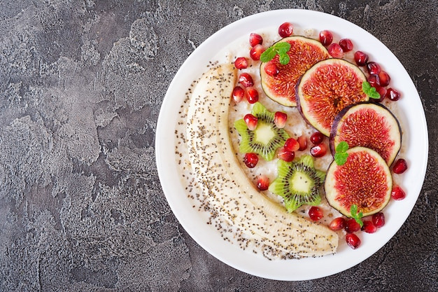 Delicious and healthy oatmeal with figs, kiwi, pomegranate, banana and chia seeds. Premium Photo