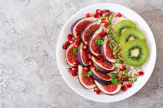 Delicious and healthy oatmeal with figs, kiwi and pomegranate. Premium Photo