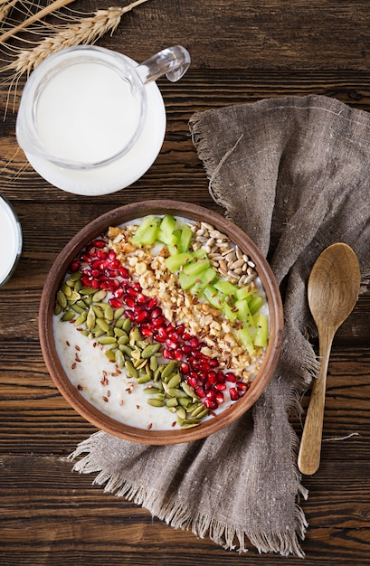 Delicious and healthy oatmeal with kiwi, pomegranate and seeds. healthy breakfast. fitness food. proper nutrition. rustic style. flat lay. top view Premium Photo