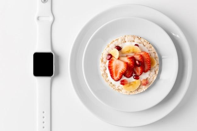 Delizioso spuntino sano e smartwatch Foto Gratuite