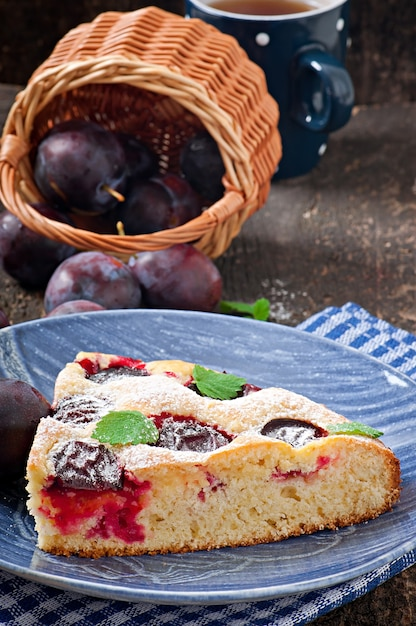 Delicious homemade cake with plums on a wooden Premium Photo