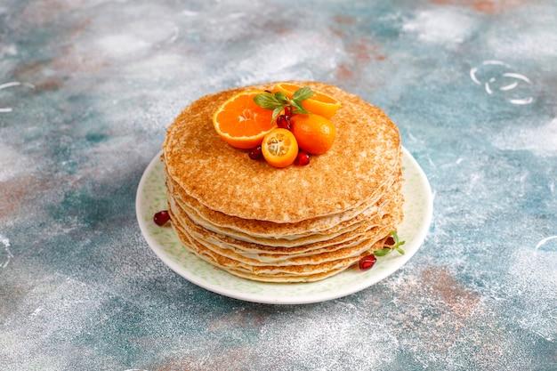 Вкусный домашний креповый торт, украшенный зернами граната и мандаринами. Бесплатные Фотографии