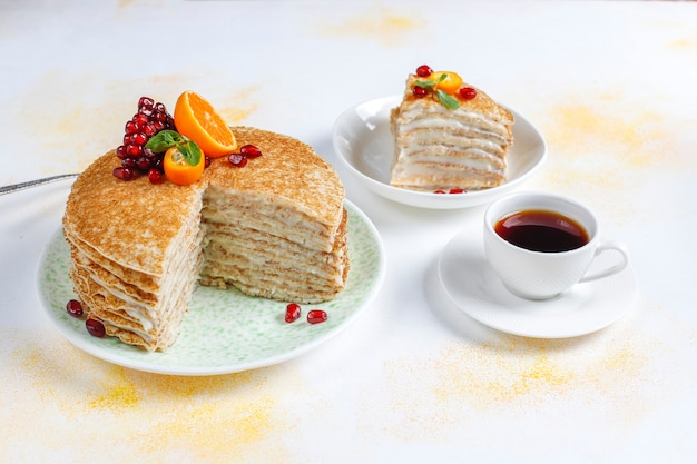 Delicious homemade crepe cake decorated with pomegranate seeds and mandarins. Free Photo
