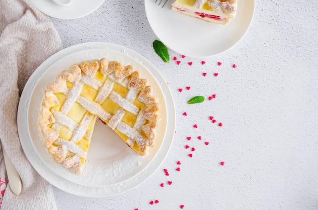 Вкусный домашний пирог из слоеного теста или торт с начинкой из сливочного сыра и вишни на белом фоне на светлом фоне камня. десерт на день святого валентина. горизонтальная ориентация. Premium Фотографии