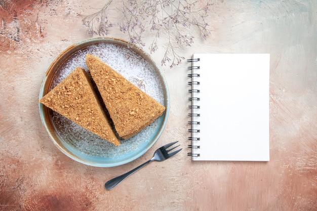 Deliziosa torta al miele all'interno del vassoio su grigio Foto Gratuite