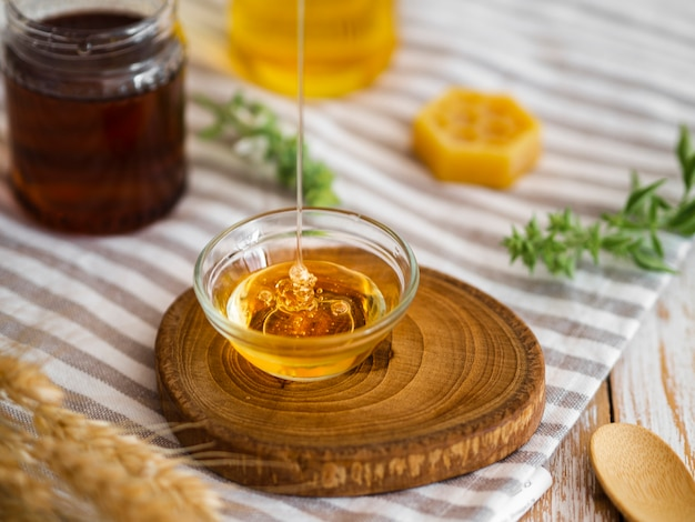 Delicious honey pouring in bowl Free Photo