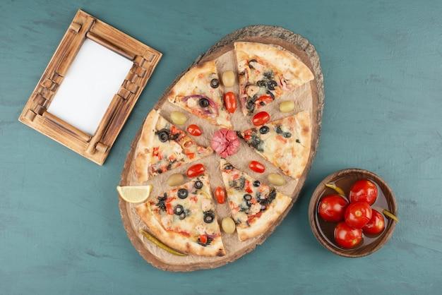 おいしいホットピザ、ピクルストマトのボウル、青いテーブルの額縁。 無料写真
