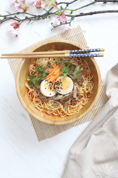 Delicious hot ramen with egg and beef on the wooden bowl with chopstick Premium Photo