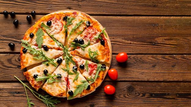 木製のテーブルに美味しいイタリアンピザ 無料写真