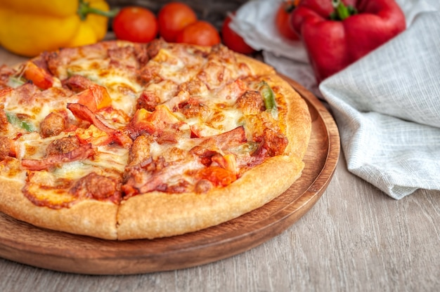 Delicious italian pizza sliced with bacon, cheese, tomato, capsicum on wooden plate Premium Photo