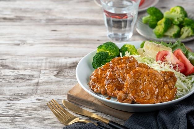 식탁에 접시에 야채와 과일 샐러드 식사와 함께 맛있는 육즙 돼지 갈비. 프리미엄 사진