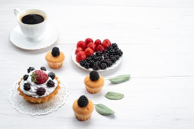 白い机の上のプレートの中にクリームとベリーのクッキーとベリーのおいしい小さなケーキ、ケーキビスケット焼きフルーツベリー 無料写真