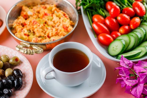 ピンクの表面にお茶、オリーブ、サラダ、花の高角度のビューが付いている鍋でおいしい食事 無料写真