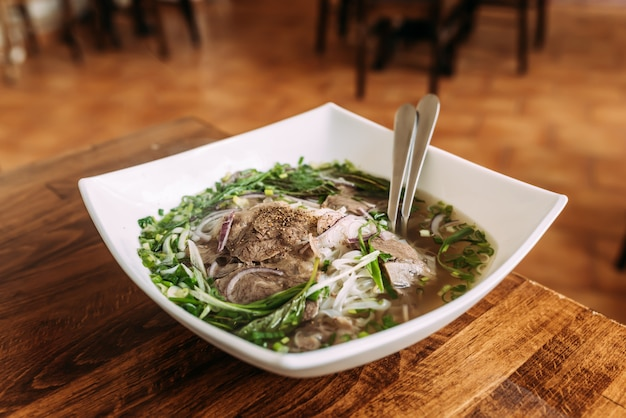 Delicious meal. soup with vegetables and meat in a white ceramic plate. pho bo. Premium Photo