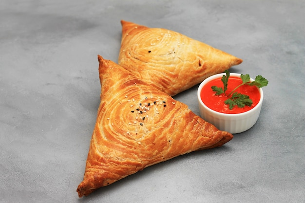 Delicious meat samosas and red sauce on gray. Premium Photo