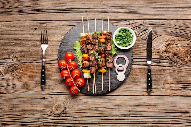Delicious meat skewer on black slate with fork and butter knife over wooden table Free Photo