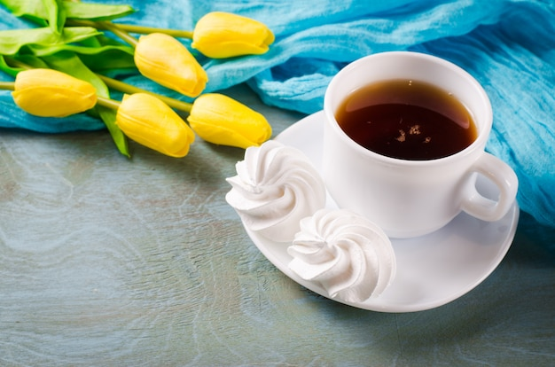 Delicious meringue cookies and cup of hot tea. Premium Photo