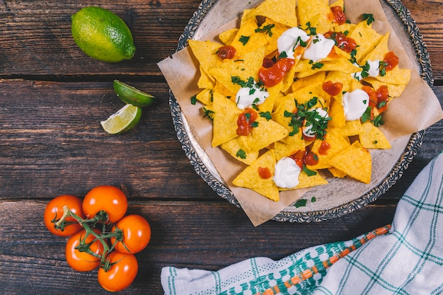 Delicious mexican nachos in plate; lemon slices; cherry tomatoes and cloth on table Free Photo