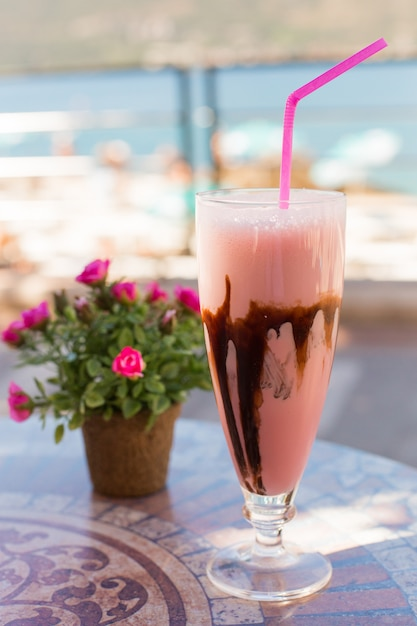 Delicious milk dessert with chocolate and strð°wberry on ceramic table and blurred background Premium Photo