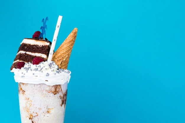 Delicious milkshake with ice cream cone and cake on blue background Free Photo