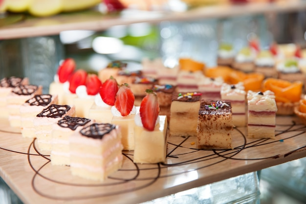 Delicious mini cakes on buffet table Free Photo