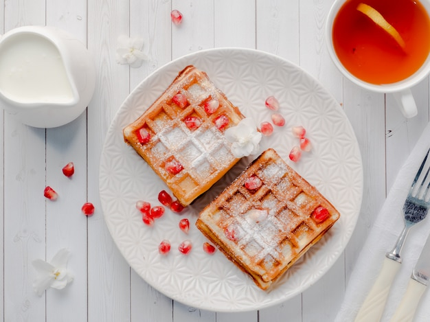 Delicious mouth-watering viennese waffles with honey and pomegranate seeds on a white plate Premium Photo