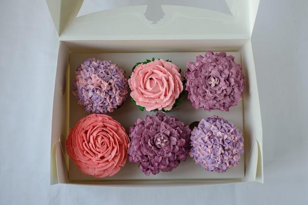 Вкусные разноцветные кексы в белой коробке. Premium Фотографии