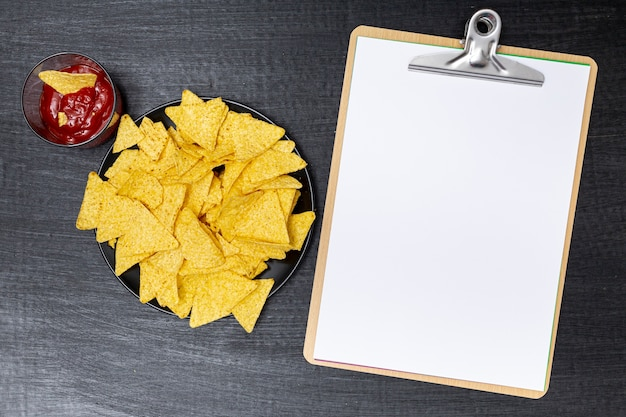 Delicious nachos with dip next to clipboard Free Photo