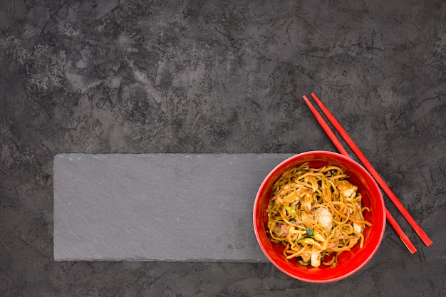 Delicious noodles on black slate with chopsticks over textured background Free Photo