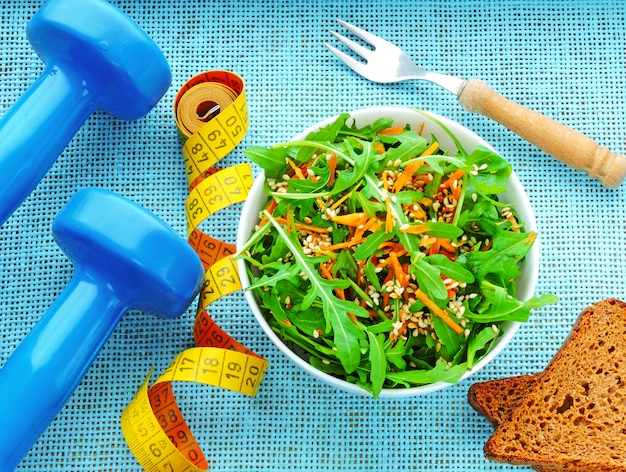Delicious and nutritious fitness salad with arugula carrots and sesame. the concept of weight loss and sports lifestyle Premium Photo