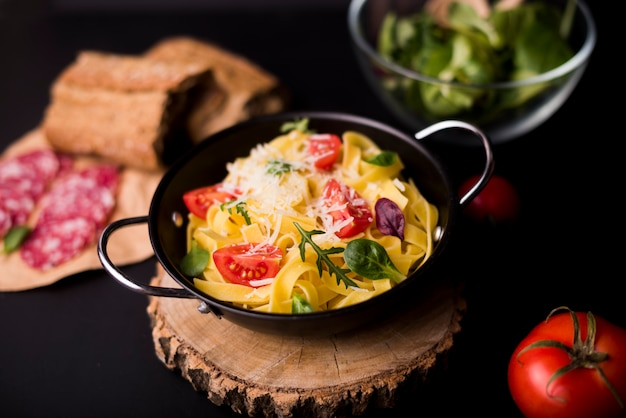 Delicious pasta for breakfast in container over wooden coaster Free Photo