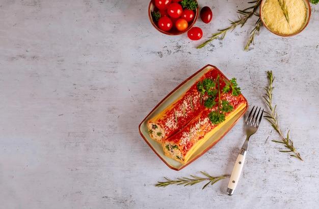 Вкусная паста каннеллони, фаршированная рикоттой и шпинатом Premium Фотографии