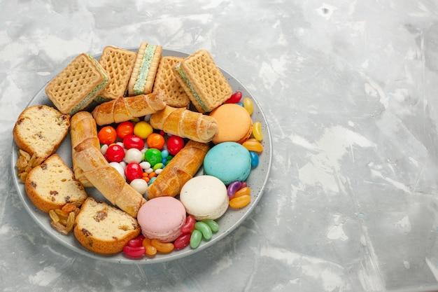 白いテーブルの上にマカロンとキャンディーのおいしいペストリー 無料写真