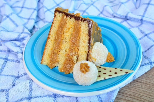 Delicious piece of dulce de leche cake with chocolate on a blue plate Premium Photo