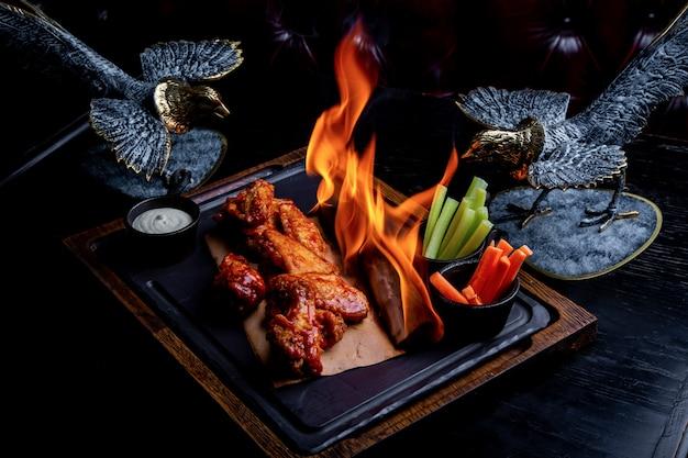 Вкусные кусочки куриных крылышек на гриле с огнем пламени. барбекю и гриль. блюдо ресторана Premium Фотографии
